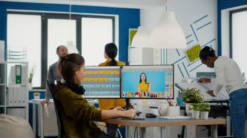 Professional woman retoucher edits assets in creative media agency office